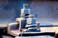 Fastening parts using bolts and nuts on the railroad track_ stock photography