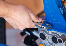 Fastening the screws on a small machine Stock Photo