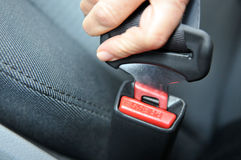 Fastening A Seat Belt. Closeup of a woman's hand as she fastens a seat belt royalty free stock photo