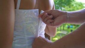 Fastening White Bride`s Wedding Dress. Preparation for wedding stock footage