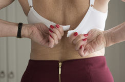 Fastening a woman's bra Stock Photo