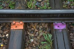 Fastenings rail to sleepers on the old railway painted in bright orange and purple colors after the rain. Close-up. Fastenings rail to sleepers on the old royalty free stock photos