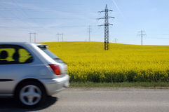 Faster... Silver car going very fast around field of yellow flowers Stock Photos