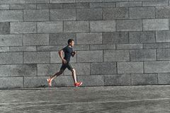 Faster than ever. Full length of young man in sports clothing running while exercising outside royalty free stock image