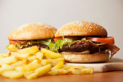 Fastfood: burgers and fries. Fastfood burgers and fries lies on wood table stock image
