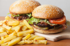 Fastfood: burgers and fries. Fastfood burgers and fries lies on wood table royalty free stock photo