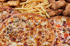 Fastfood chicken nuggets, legs, pizzas and fry potatos. Group of fastfood - chicken nuggets, legs, pizzas and fry potatos Royalty Free Stock Images