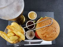 Fastfood chips burger sauces beer plate cutlery Royalty Free Stock Photo