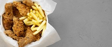 Fastfood: fried chicken drumsticks, spicy wings, French fries and chicken strips in paper box over gray background, top view. Copy. Space stock photos