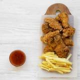 Fastfood: gebratenes Hühnertrommelstöcke, würzige Flügel, Pommes-Frites und Hühnerfinger mit sauer-süßer Soße über weißer Holzobe stockfoto