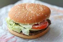 Fastfood hamburger. Bun on paper wrapper royalty free stock photos