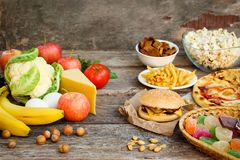 Fastfood and healthy food. Concept choosing correct nutrition or of junk eating. Fastfood and healthy food on old wooden background. Concept choosing correct royalty free stock images