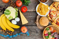 Fastfood and healthy food on old wooden background. Concept choosing correct nutrition or of junk eating. Top view stock photos