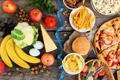 Fastfood and healthy food on old wooden background. Concept choosing correct nutrition or of junk eating. Top view stock photo