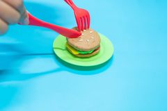 Fastfood model. Fastfood model with hamburger chesse on plastic blue table background, play dought at home, child care cooking food model, educational toys for royalty free stock images