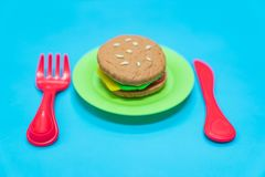 Fastfood model. Fastfood model with hamburger chesse on plastic blue table background, play dought at home, child care cooking food model, educational toys for stock images