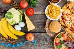 Fastfood och sund mat på gammal träbakgrund Begrepp som väljer korrekt näring eller av att äta för skräp arkivfoton