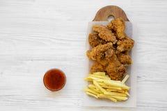Fastfood: stekt kycklingtrumpinnar, kryddiga vingar, pommes frites och fega remsor med sur-sötsak sås över vit träyttersida, arkivfoton