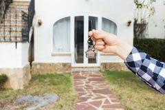 Fastighet- och egenskapsbegrepp - handen rymmer hustangenter på hus formade keychain framme av ett nytt hem royaltyfri bild