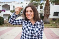 Fastighet- och egenskapsbegrepp Lycklig äganderätt Attraktiv ung kvinna som rymmer tangenter, medan stå utomhus- mot royaltyfri bild
