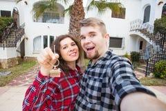 Fastighet- och egenskapsbegrepp - lyckligt par som rymmer tangenter till den nya hem- och husminiatyren fotografering för bildbyråer