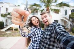 Fastighet- och egenskapsbegrepp - lyckligt par som rymmer tangenter till den nya hem- och husminiatyren royaltyfri fotografi