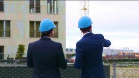 Fastighetbärare i hjälmar nytt kontor f?r konstruktion Säkra affärsmän och arkitekt som framme talar av stock video