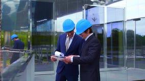 Fastighetbärare i hjälmar nytt kontor f?r konstruktion Säkra affärsmän och arkitekt som framme talar av lager videofilmer