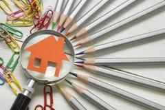 Fastighetbegrepp - förstoringsglas, blyertspennor och modellhus på trätabellen arkivbild