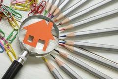 Fastighetbegrepp - förstoringsglas, blyertspennor och modellhus på trätabellen royaltyfria foton