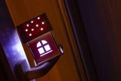 Fastighetbegrepp med ett trähus för liten leksak på fönsterhandtaget Idén av begreppet av fastigheten, personlig egenskap royaltyfri fotografi