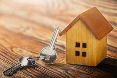 Fastighetbegrepp med trähuset för liten leksak och tangent på träbakgrund Idé för fastighetbegreppet, personlig egenskap royaltyfri bild