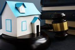 Fastighetlag Modell av huset, auktionsklubban och böcker royaltyfria bilder
