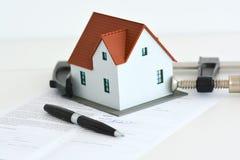 Fastighetpriser eller krisbegrepp med huset i ett klämmahjälpmedel Arkivfoto
