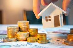 Fastighetsinvestering coins sparande för stapel för begreppshandpengar skyddande arkivfoto