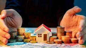 Fastighetsinvestering coins sparande för stapel för begreppshandpengar skyddande arkivfoton