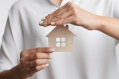 Fastighetsmäklare för ung kvinna för stående för begreppsdollaren för 100 bills det gjorda huset intecknar ut Arkivfoton