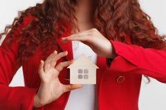 Fastighetsmäklare för ung kvinna för stående för begreppsdollaren för 100 bills det gjorda huset intecknar ut Fotografering för Bildbyråer