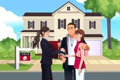 Fastighetsmäklare framme av ett sålt hus med hennes kund stock illustrationer