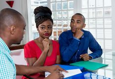 Fastighetsmäklare i konsultation med afrikansk amerikanpar royaltyfria bilder