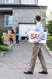 fastighetsmäklare med försäljningstecknet som framme går av folk som flyttar sig in i Royaltyfri Fotografi