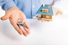 Fastighetsmäklare med husmodellen och tangenter i händer Fotografering för Bildbyråer