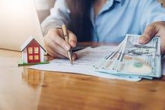 Fastighetsmäklare med husmodellen som rymmer pengar och pekar pennan royaltyfria foton