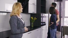Fastighetsmäklare och par som talar på kökstudion arkivfilmer