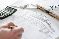 Fastighetsmäklare som analyserar finansiell planläggning av ett hus Royaltyfri Bild