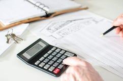 Fastighetsmäklare som analyserar finansiell planläggning av ett hus Arkivbilder