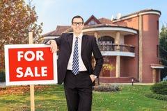 Fastighetsmäklare som annonserar ett till salu hus arkivfoto