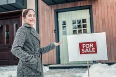 Fastighetsmäklare som bär varmt laganseende utanför trevligt stort hus arkivfoto