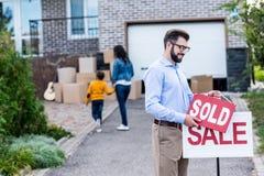 fastighetsmäklare som framme hänger det sålda tecknet av folk som flyttar sig in i Royaltyfri Foto