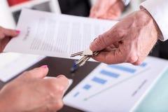 Fastighetsmäklare som ger hustangenter till hans klient Arkivbild